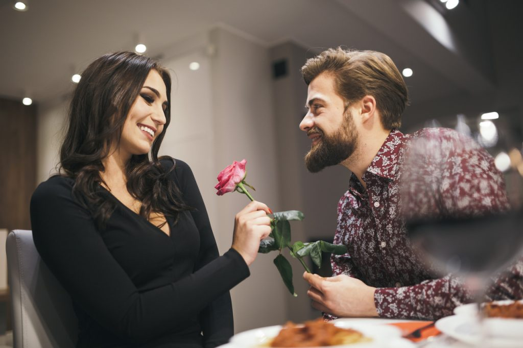 A man surprising his partner with a red rose