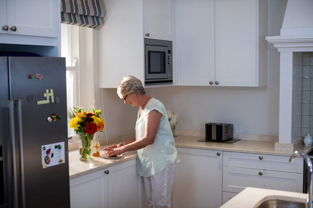 A woman preparing to put her vase of flowers in the refrigerator